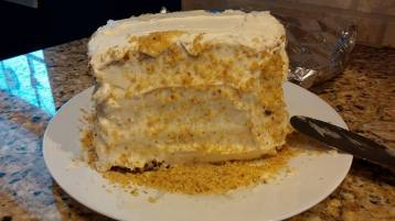 layered cake, with cream cheese frosting, and walnut crumble on the outside